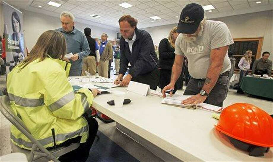 In this Thursday, April 3, 2013, photo, people fill out applications at the Green Mountain Flagging table at the 4th Annual Central Vermont Job Fair in Montpelier, Vt. The Labor Department reports on the number of Americans who applied for unemployment benefits in the last week on Thursday, April 18, 2013. (AP Photo/Toby Talbot) Photo: AP / AP