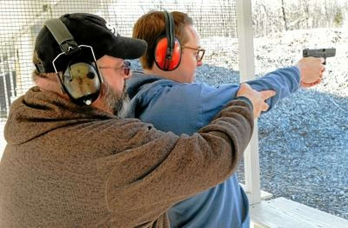 Michael Bellmore, New Haven Register reporter, gets instruction from certified NRA Instructor Michael Peart of Meriden while shooting a Glock 19 9mm semiautomatic pistol during the shooting portion of his NRA Basic Pistol Safety Course. Bellmore is getting a Connecticut Pistol Permit. Thursday, February 7, 2013. Photo by Peter Hvizdak / New Haven Register