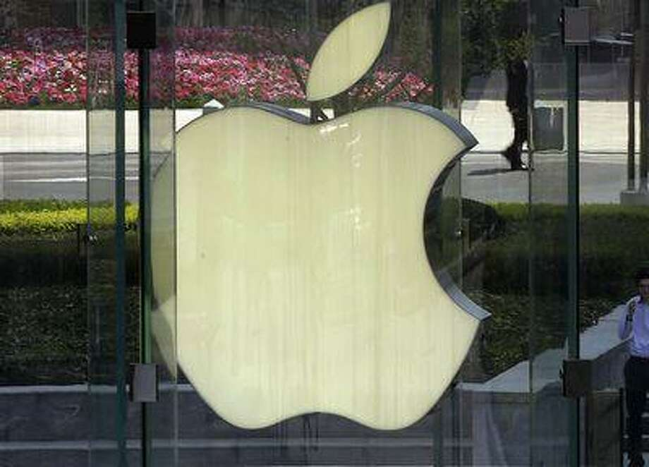 In this April 2, 2013, file photo, a man smokes near the logo of Apple in Shanghai, China. Photo: AP / AP net