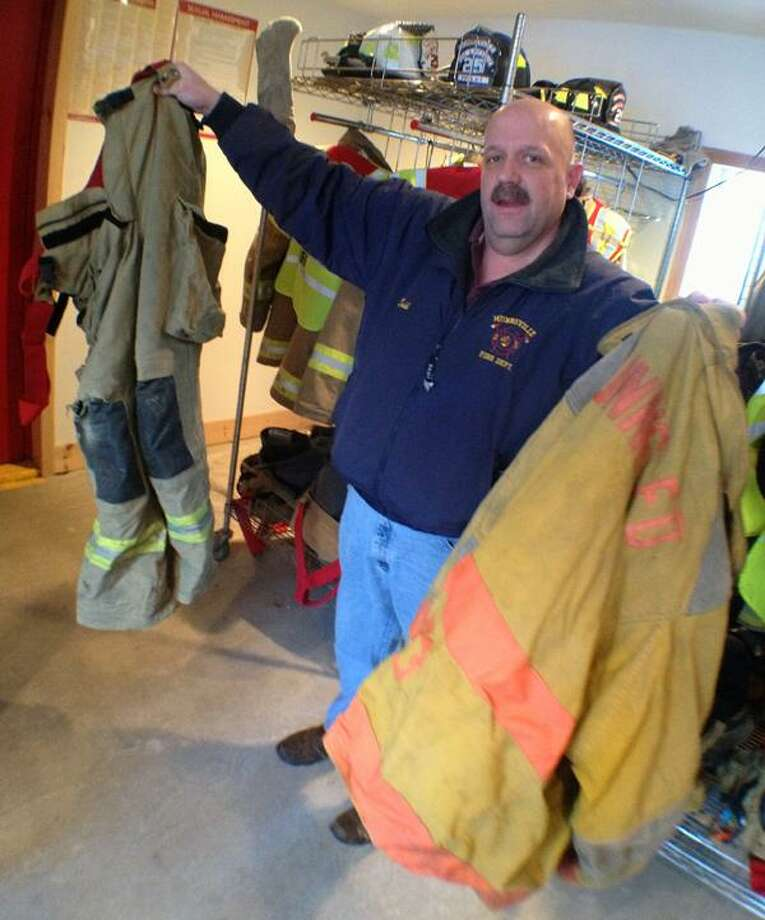 """Dispatch Staff Photo by JOHN HAEGER <a href=""""http://twitter.com/oneidaphoto"""">twitter.com/oneidaphoto</a> Munnsville Fire Chief Todd Collins holds some of the old turnout gear that will be replaced through a grant   on Friday, Jan. 18, 2013."""