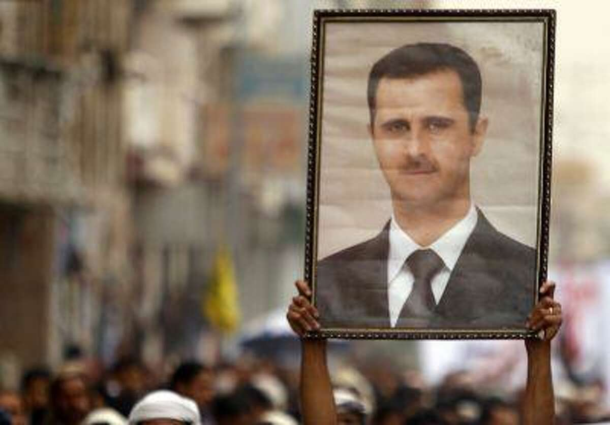 A Shi'ite anti-government protester holds up a poster of Syrian President Bashar al-Assad during a demonstration against Israeli air strikes in Syria, in Sanaa May 10, 2013.