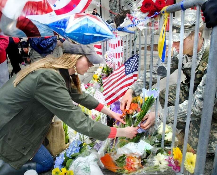 Boston-National Guard Lt. Garrett Robinson, of Kittery, Maine (R)  helps a woman who did not wish to be identified place flowers at a memorial on Boylston Street.  Melanie Stengel/Register
