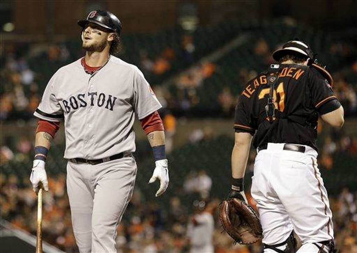 Boston Red Sox' Jarrod Saltalamacchia, left, walks off the field past Baltimore Orioles catcher Taylor Teagarden after striking out in the second inning of a baseball game in Baltimore, Friday, Sept. 28, 2012. (AP Photo/Patrick Semansky)