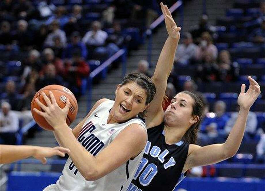 Connecticut's Stefanie Dolson, left, grabs a rebound from Holy Family's Kelly Brady during the first half of an exhibition NCAA college basketball game in Hartford, Conn., on Wednesday, Nov. 7, 2012. (AP Photo/Fred Beckham) Photo: AP / FR153656 AP