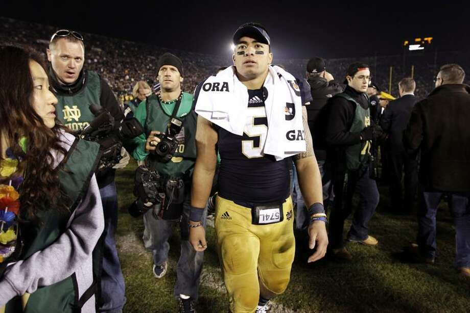 FILE - In this Nov. 17, 2012, file photo, Notre Dame linebacker Manti Te'o walks off the field following an NCAA college football game against Wake Forest in South Bend, Ind. A story that Te'o's girlfriend had died of leukemia _ a loss he said inspired him to help lead the Irish to the BCS championship game _ was dismissed by the university Wednesday, Jan. 16, 2013, as a hoax perpetrated against the linebacker. (AP Photo/Michael Conroy, File) Photo: AP / A2012