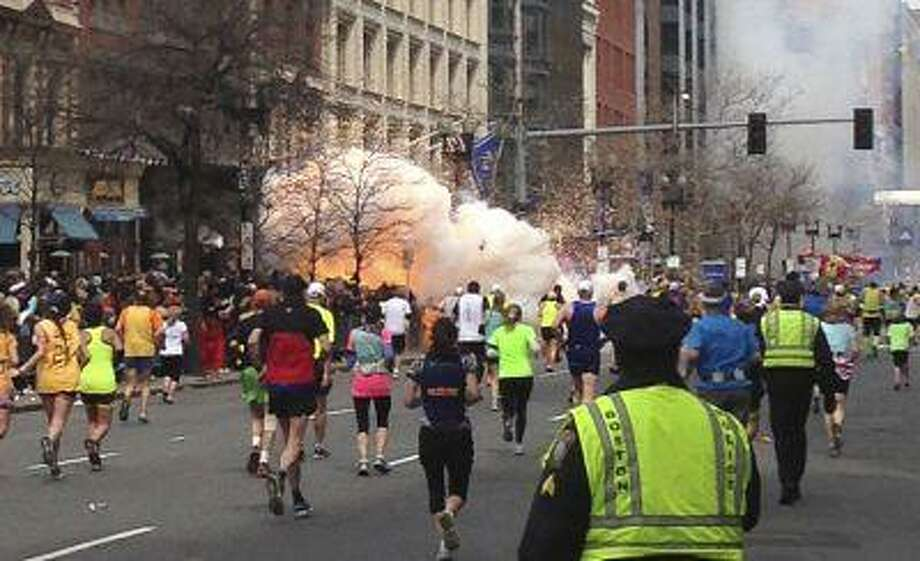 Runners continue to run towards the finish line of the Boston Marathon as an explosion erupts near the finish line of the race in this photo exclusively licensed to Reuters by photographer Dan Lampariello after he took the photo in Boston, Massachusetts, April 15, 2013. Two simultaneous explosions ripped through the crowd at the finish line of the Boston Marathon on Monday, killing at least two people and injuring dozens on a day when tens of thousands of people pack the streets to watch the world famous race. REUTERS EXCLUSIVE Mandatory Credit REUTERS/Dan Lampariello (UNITED STATES - Tags: CRIME LAW SPORT ATHLETICS) MANDATORY CREDIT Photo: REUTERS / X80002
