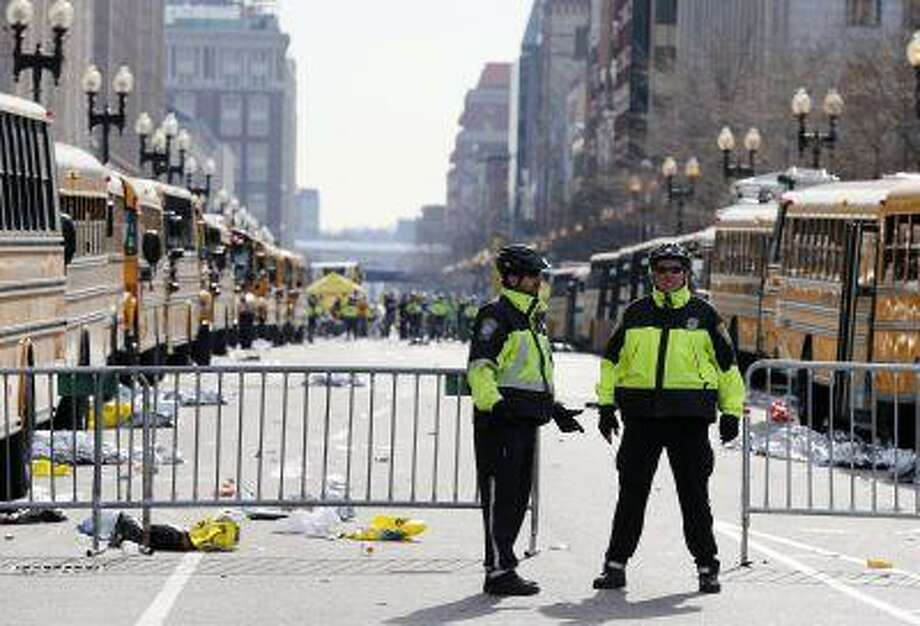 Boston police officers stand on Boylston Street near empty buses meant to transport runners who were instead diverted from the course following an explosion at the finish line, Monday, April 15, 2013, in Boston. (AP Photo/Michael Dwyer) Photo: AP / AP