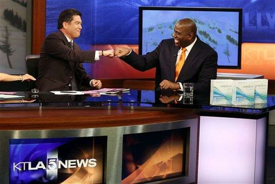 """Earvin """"Magic"""" Johnson, CEO of Magic Johnson Enterprises, right, discusses the OraQuick In-Home HIV test and the importance of knowing your HIV status with anchor Frank Buckley on the set of the KTLA Morning News Show on Monday, March 25, 2013 in Los Angeles.  (Photo by Matt Sayles/Invision for OraQuick/AP Images) / 2013 Invision"""
