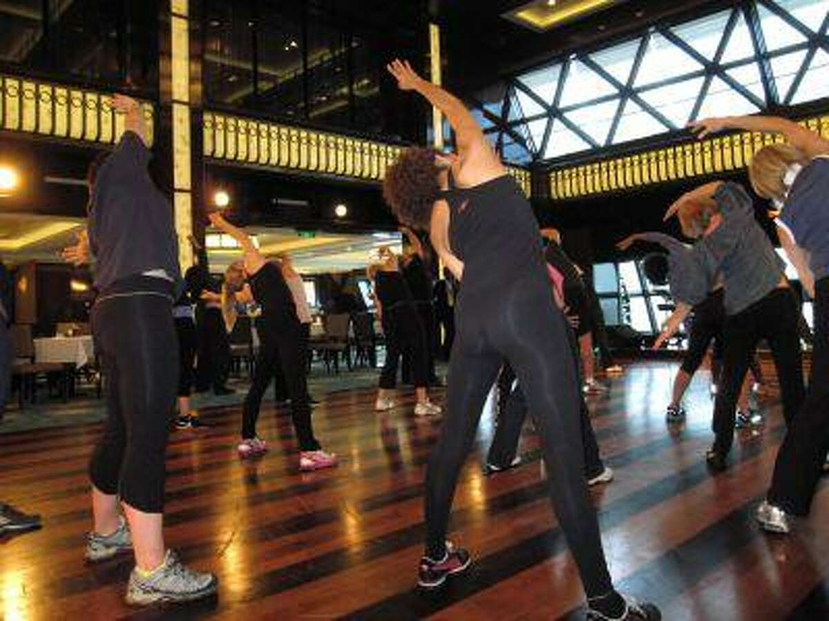 This May 9, 2013 photo shows a fitness class designed by the athletic trainer for the Rockettes, Elaine Winslow, and taught to passengers aboard the Norwegian Breakaway cruise ship. The Rockettes, famed for their kick line at the Radio City Music Spectacular, are the godmothers for the ship. (AP Photo/Beth J. Harpaz)