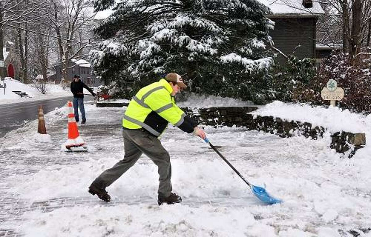 Newtown--Workers from L.R.M. Landscapers shovel snow off the small plaza downtown, that until several weeks ago was inundated with thousands of stuffed animals, flowers and candles remembering the Sandy Hook shooting victims. Photo-Peter Casolino 1/16/13