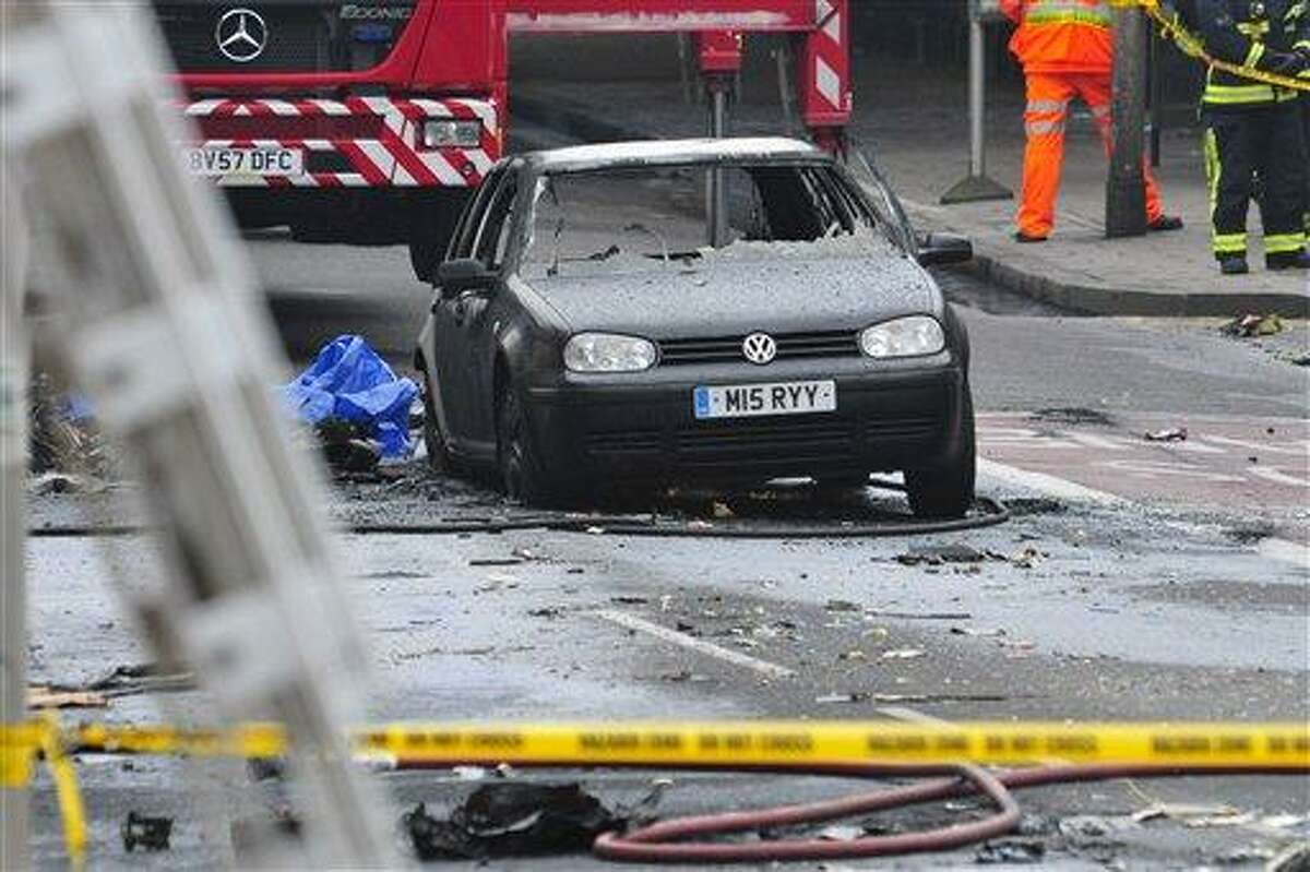A damaged car remains in the street after a helicopter crashed into a construction crane on top of St George's Wharf tower building, in London, Wednesday. Police say two people were killed when a helicopter crashed during rush hour in central London after apparently hitting a construction crane on top of a building.AP Photo/Vince Pol