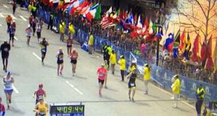 In a photo given to the New Haven Register, Alan Hagyard,  far left front  running with blue shorts, blue cap and white shirt with bomb blast far right in photo, who was a runner near the Boston Marathon finish line when a bomb exploded there yesterday, recounts his experience.  Tuesday  April 15, 2013  at his Hamden, Connecticut home.  Photo by Peter Hvizdak / New Haven Register Photo: New Haven Register / ©Peter Hvizdak /  New Haven Register
