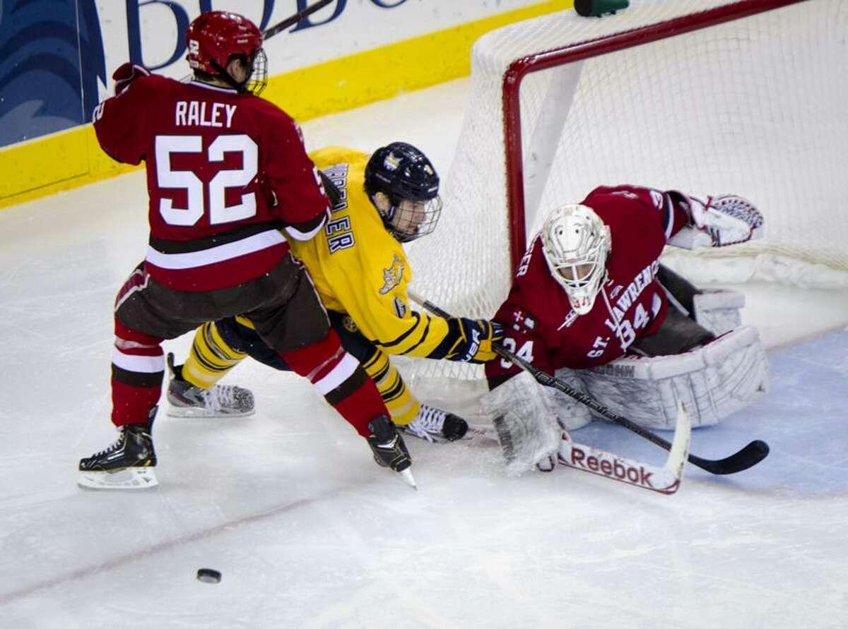 Sports-Quinnipiac/St. Lawrence Hockey 2nd period. St. Lawrence's Pat Raley helps goalie Matt weninger defend against Cory Hibbler. Melanie Stengel/Register2/15/13