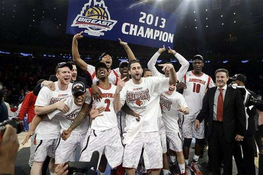 Louisville's Russ Smith (2), Gorgui Dieng (10) and Luke Hancock, center, celebrate with the team after their 78-61 win over Syracuse in an NCAA college basketball championship game at the Big East Conference tournament, Saturday, March 16, 2013, in New York. (AP Photo/Frank Franklin II) Photo: AP / AP