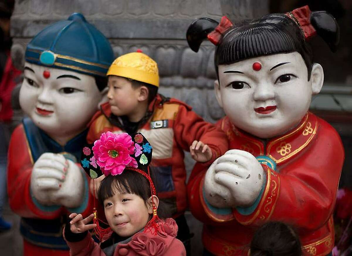 Children wearing traditional Chinese hats pose with a pair of statues on display at a shopping district in Beijing Thursday, Feb. 14, 2013. (AP Photo/Andy Wong)