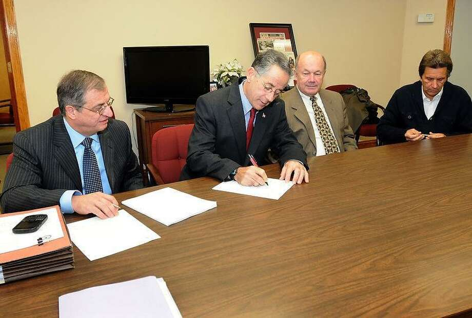 The Town of East Haven, its police and police commission sign a consent letter from the Department of Justice in Mayor Joe Maturo office Thursday, November 15, 2012,  detailing an agreement to rebuilding  the East Haven Police department. From left in photo are Attorney Larry Sgrignari, representing the Town of East Haven, Mayor Joe Maturo, East Haven Police Chief Brent Larrabee and East Haven Police Commission Chairman Joseph Civitello. The standards to be enforced include specific plans to create biased-free policing, monitor use of force, searches and seizure, guidance on policies and training, ways to handle and measure civilian complaints, plans for supervision and management and community engagement or oversight. Photo by Peter Hvizdak / New Haven Register Photo: New Haven Register / ©Peter Hvizdak /  New Haven Register