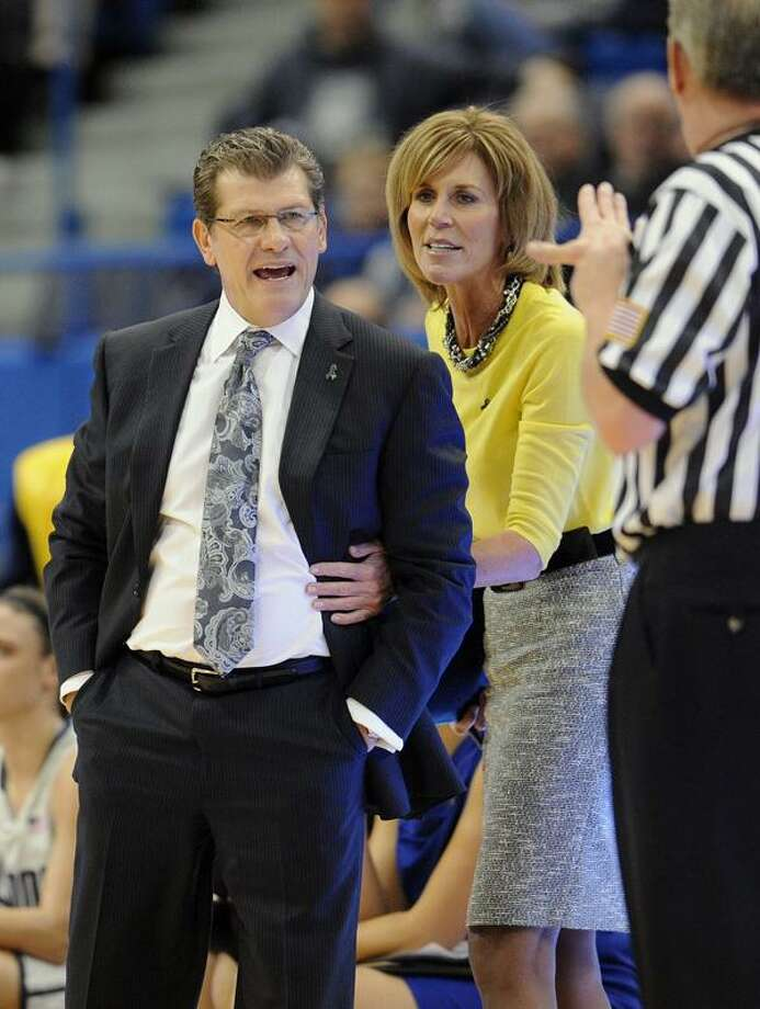 Connecticut head coach Geno Auriemma, left, is held back by associate head coach Chris Dailey, center, as he argues a call with an official during the first half of an NCAA college basketball game in Hartford, Conn., Tuesday, Jan. 15, 2013. (AP Photo/Jessica Hill) Photo: AP / A2013