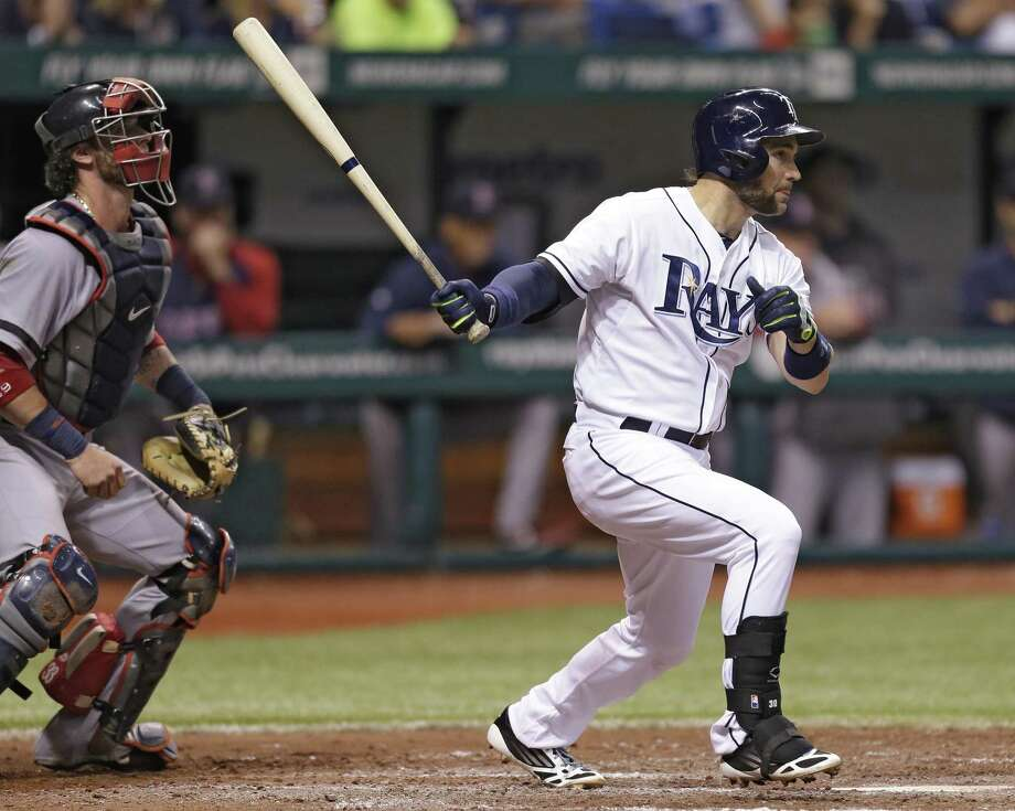 Tampa Bay Rays' Luke Scott, right, follows the flight of his sixth-inning RBI single off Boston Red Sox relief pitcher Andrew Miller during a baseball game Thursday, May 16, 2013, in St. Petersburg, Fla. Rays' Jose Lobaton scored on the hit. Catching for Boston is Jarrod Saltalamacchia. (AP Photo/Chris O'Meara) Photo: AP / AP