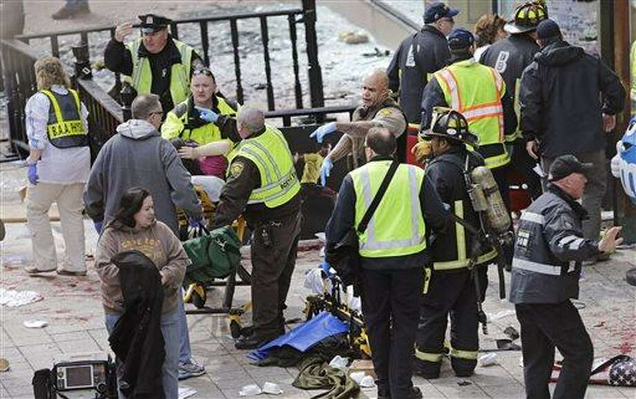 Medical workers aid injured people at the finish line of the 2013 Boston Marathon following explosions in Boston, Monday, April 15, 2013. Two explosions shattered the euphoria of the Boston Marathon finish line on Monday, sending authorities out on the course to carry off the injured while the stragglers were rerouted away from the smoking site of the blasts. (AP Photo/Charles Krupa) Photo: AP / AP