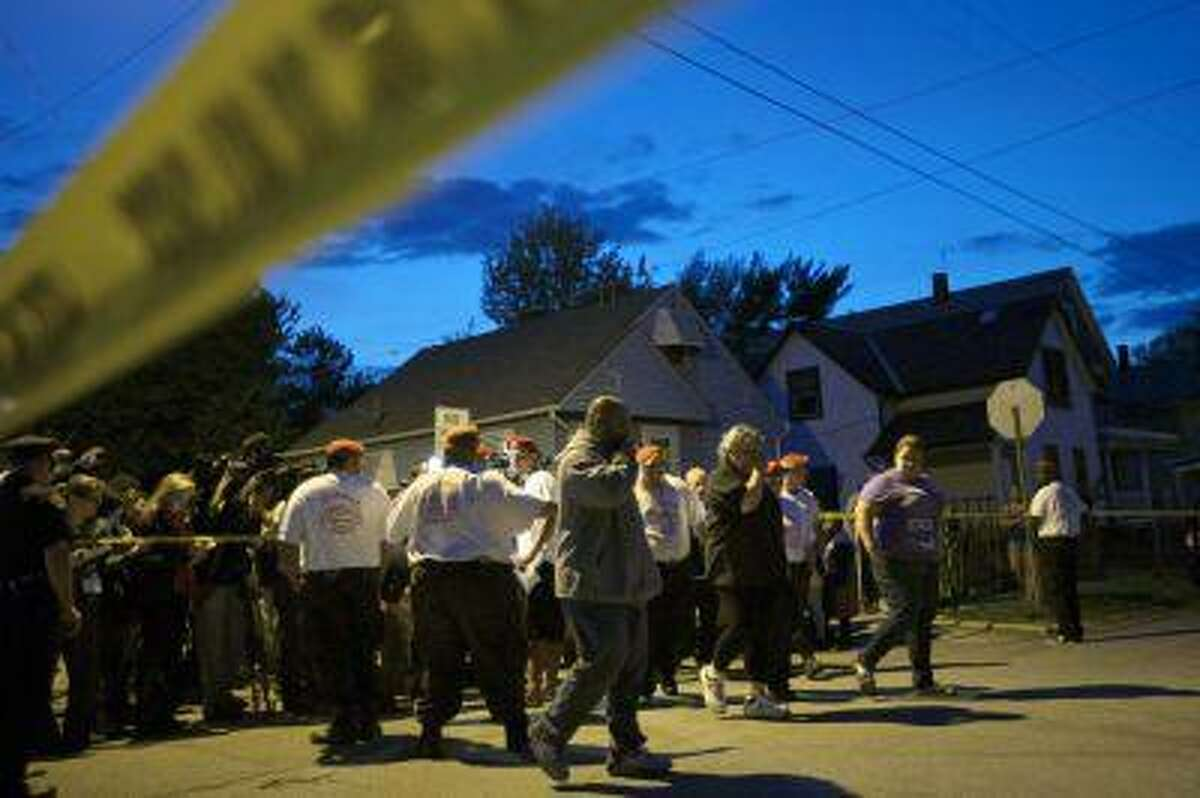 Ricky DeJesus (center, in gray) and his aunt, Sandra Ruiz, return to the family home of Georgina DeJesus after speaking with the media in Cleveland, May 7, 2013. Georgina DeJesus was one of three Cleveland women found alive after vanishing in their own neighborhood for about a decade ago.