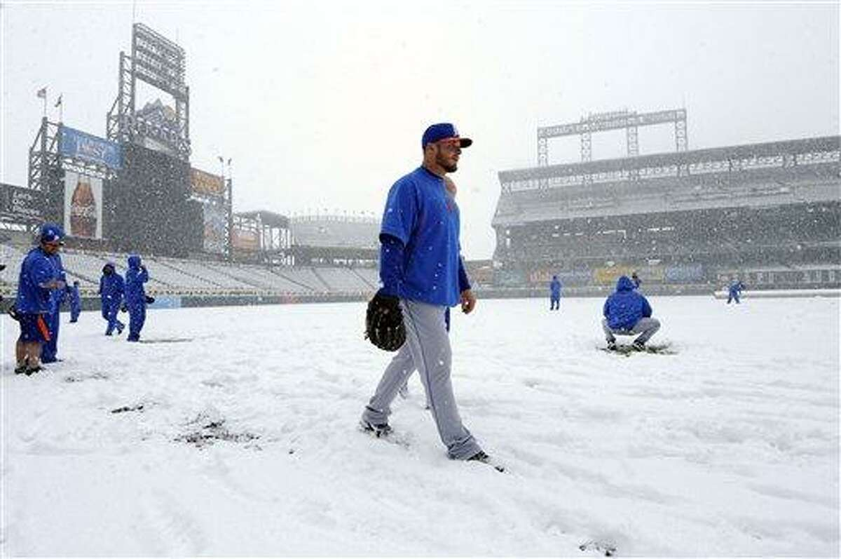 A new York Mets pitcher walks in the snow before a scheduled baseball game against the Colorado Rockies, Monday, April 15, 2013, in Denver. The game has been canceled. (AP Photo/Jack Dempsey)