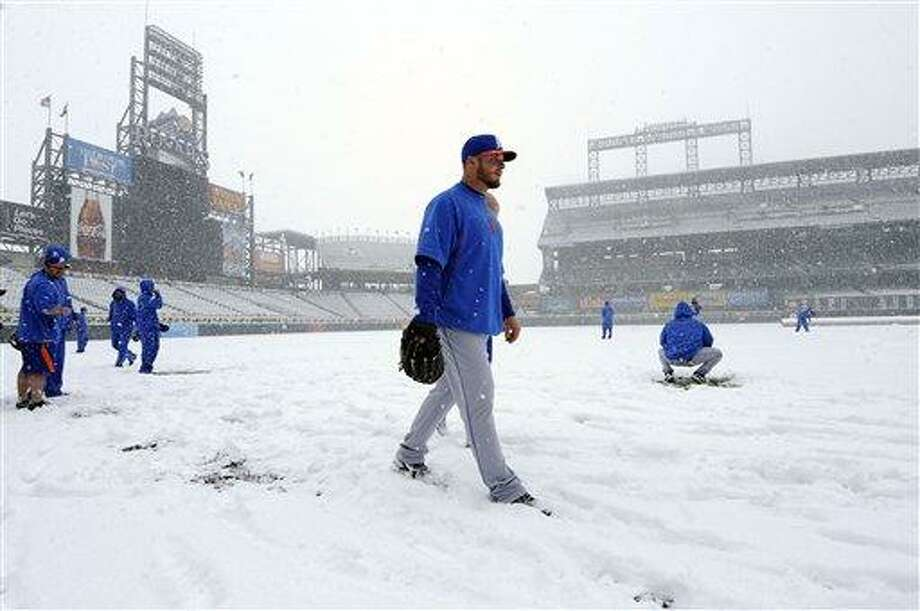 A new York Mets pitcher walks in the snow before a scheduled baseball game against the Colorado Rockies, Monday, April 15, 2013, in Denver. The game has been canceled. (AP Photo/Jack Dempsey) Photo: AP / FR42408 AP