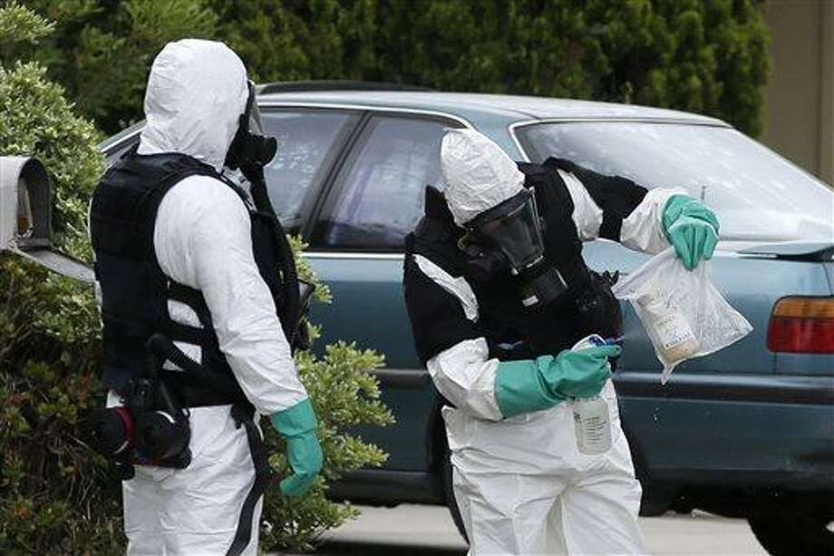 An investigator sprays on a bag containing a bottle collected from a home in Costa Mesa, Calif., Monday, April 15, 2013. A man was blown up in the home  Sunday evening and at least 16 neighbors were evacuated as authorities found and destroyed other explosive devices, police said Monday. (AP Photo/Jae C. Hong) Photo: AP / AP