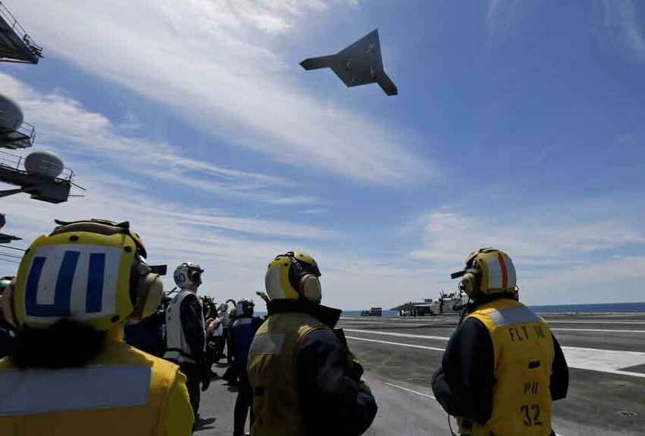 A Navy X-47B drone does a fly by the nuclear powered aircraft carrier USS George H. W. Bush after it was launched from the carrier off the coast of Virginia, Tuesday, May 14, 2013. (AP Photo/Steve Helber) Photo: ASSOCIATED PRESS / AP2013
