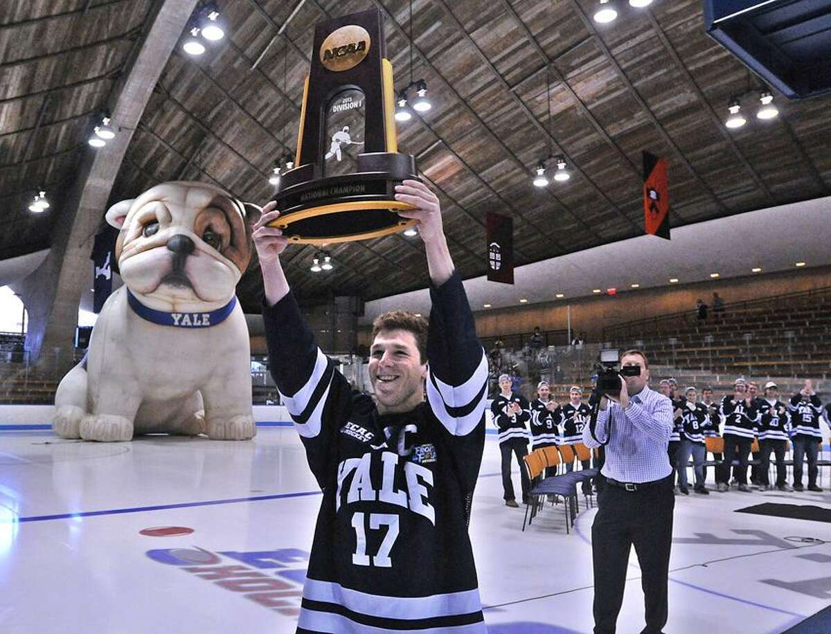 New Haven-- Yale's Andrew Miller carries the NCAA Hockey National Championship trophy into Ingalls Rink as they held a ceremony for the returning champions. Photo-Peter Casolino/Register pcasolino@newhavenregister.com