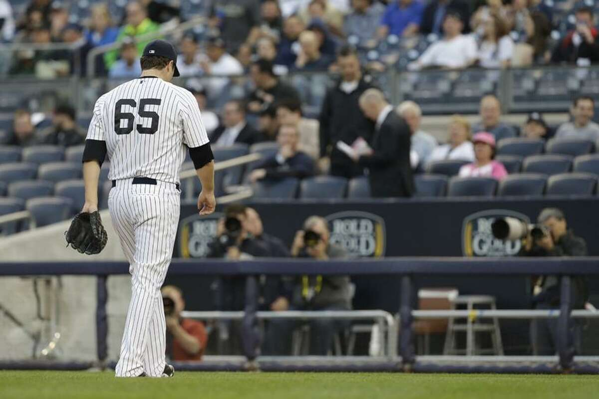 New York Yankees starting pitcher Phil Hughes walks off the field after being pulled from the game during the first inning of a baseball game against the Seattle Mariners at Yankee Stadium in New York, Wednesday, May 15, 2013. (AP Photo/Julio Cortez)