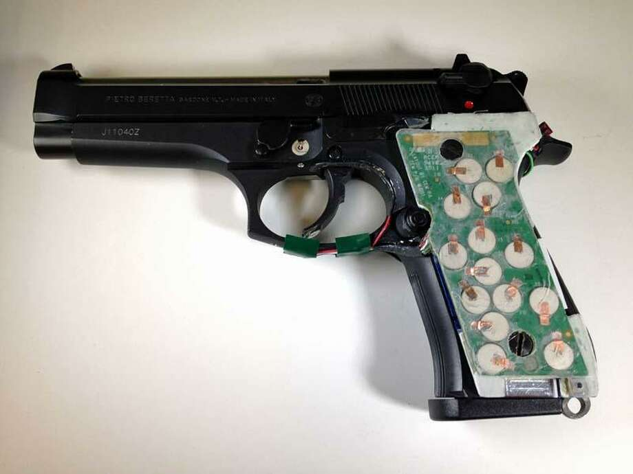 This photo provided by the New Jersey Institute of Technology shows a 9 mm semi-automatic handgun configured with transducers to its handle that can detect the grasp of an authorized user. To gun rights groups, the idea of using technology to control who can fire a gun smacks of a limitation on personal rights, particularly if it might be mandated by government. At the same time, some gun control advocates worry that such technology, by making guns appear falsely safe, would encourage Americans to stock up on even more weapons then they already have in their homes. (AP Photo/NJIT) Photo: AP / NJIT