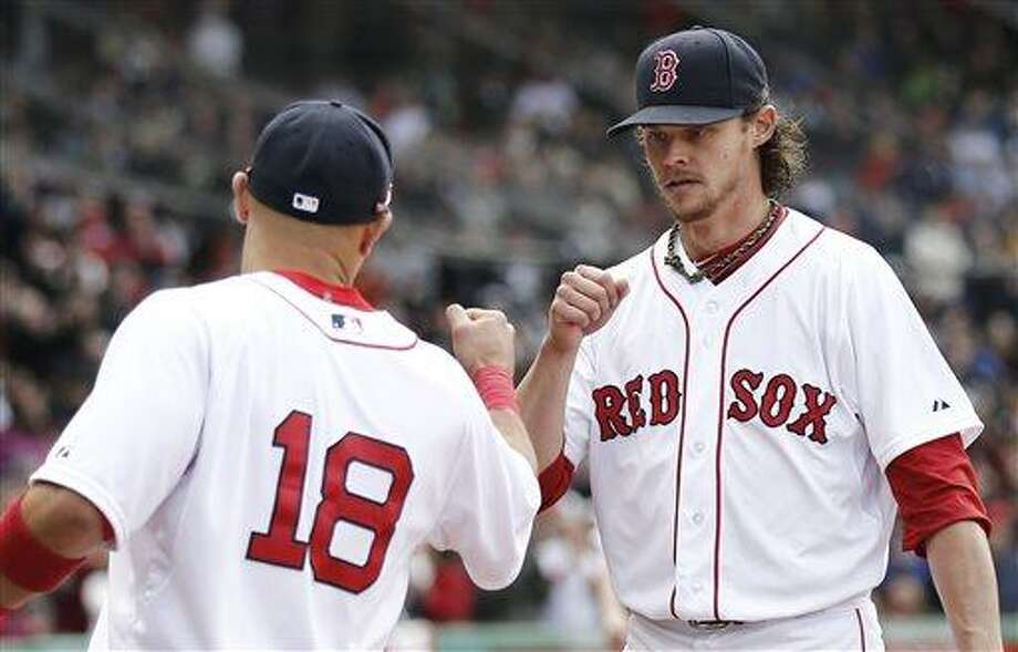Boston Red Sox starting pitcher Clay Buchholz fist bumps with Shane Victorino (18) while leaving the field after losing his no hitter the eighth inning of a baseball game against the Tampa Bay Rays at Fenway Park in Boston Sunday, April 14, 2013. (AP Photo/Winslow Townson) Photo: AP / FR170221 AP