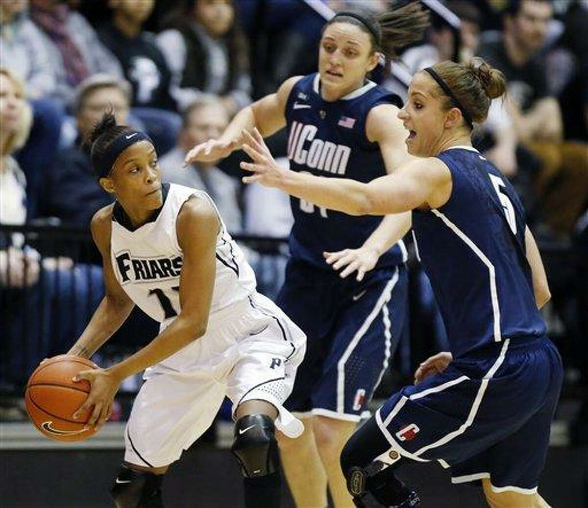 Providence's Symone Roberts (12), a former standout at New Britain High, keeps the ball away from Connecticut's Kelly Faris, center, and Caroline Doty (5) in the first half of an NCAA college basketball game in Providence, R.I., Tuesday, Feb. 12, 2013. (AP Photo/Michael Dwyer)
