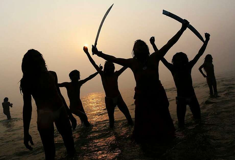 Indian Hindu holy men, or Sadhus, are silhouetted as they celebrate in the water at Sangam, the confluence of the rivers Ganges, Yamuna and mythical Saraswati, during the royal bath on Makar Sankranti at the start of the Maha Kumbh Mela in Allahabad, India, Monday, Jan. 14, 2013. Millions of Hindu pilgrims are expected to take part in the large religious congregation that lasts more than 50 days on the banks of Sangam during the Maha Kumbh Mela in January 2013, which falls every 12th year. (AP Photo/Kevin Frayer) Photo: AP / AP