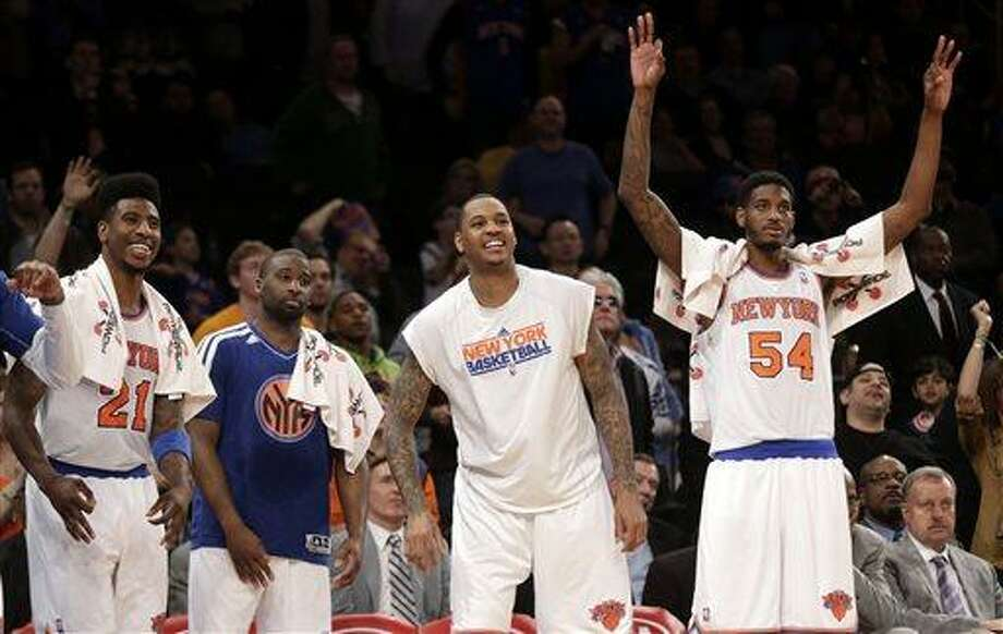 New York Knicks' Iman Shumpert, left, Raymond Felton, second from left, Carmelo Anthony, second from right, and Solomon Jones react as they watch the end of the game from the bench during the second half of the NBA basketball game against the Indiana Pacers Sunday April 14, 2013, in New York. The Knicks beat the Pacers 90-80. (AP Photo/Seth Wenig) Photo: AP / AP