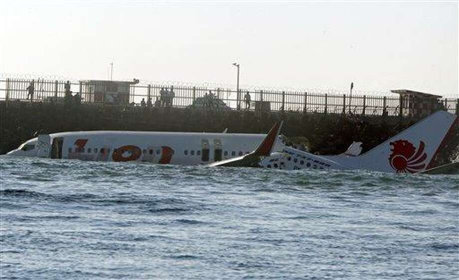 The wreckage of a Lion Air jet sits in the ocean near the airport in Bali, Indonesia on Sunday, April 14, 2013. All 108 passengers and crew survived after the new Lion Air jet crashed into the ocean and snapped into two while attempting to land Saturday on the Indonesian resort island of Bali, injuring up to 45 people. (AP Photo/Firdia Lisnawati) Photo: AP / AP