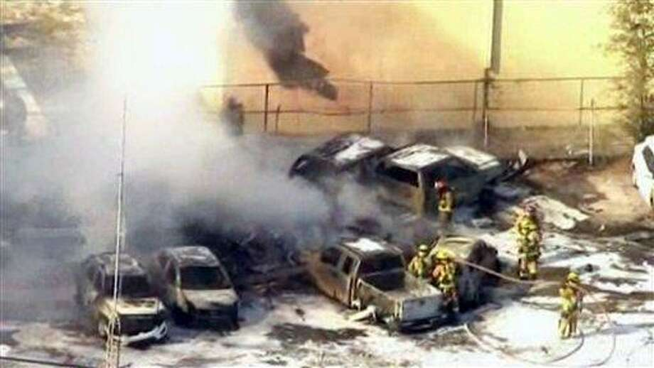 In this image taken from video, first responders work to extinguish burning vehicles after a small plane crashed into a parking lot near Fort Lauderdale Executive Airport in Fort Lauderdale, Fla. Friday afternoon, March 15, 2013, killing all three people onboard and burning about a dozen cars. No one on the ground was hurt. (AP Photo/APTN) Photo: AP / APTN/ABC