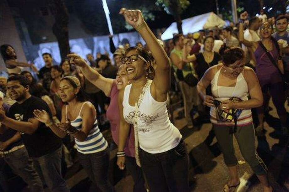 """Opposition supporters chant, """"Si se puede, Capriles presidente,"""" or """"Yes we can, Capriles president,"""" at ruling party supporters outside a polling station that had remained open about 20 minutes past the allotted time, in Caracas, Venezuela, Sunday, April 14, 2013.  (AP Photo/Ariana Cubillos) Photo: AP / AP"""