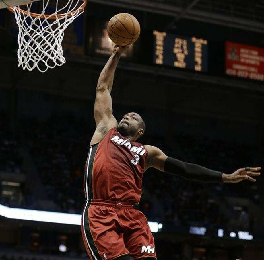 Miami Heat's Dwyane Wade goes in for a dunk against the Milwaukee Bucks in the second half of an NBA basketball game Friday, March, 15, 2013, in Milwaukee. (AP Photo/Jeffrey Phelps) Photo: AP / FR59249 AP