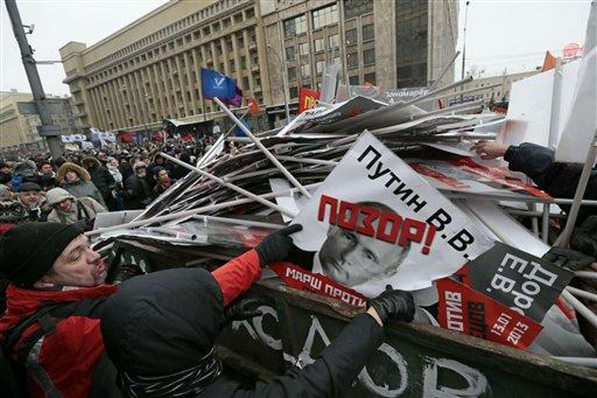 """People throw portraits brought to the rally in the garbage during a protest rally in Moscow, Russia, Sunday with the portrait of Russian President Vladimir Putin in the center. Thousands of people are gathering in central Moscow for a protest against Russia's new law banning Americans from adopting Russian children. They carry posters of President Vladimir Putin and members of Russia's parliament who overwhelmingly voted for the law last month. The posters have the word """"Shame"""" written in red over the faces and proclaim that Sunday's demonstration is a """"March Against the Scum"""" who enacted the law. AP Photo/Ivan Sekretarev"""