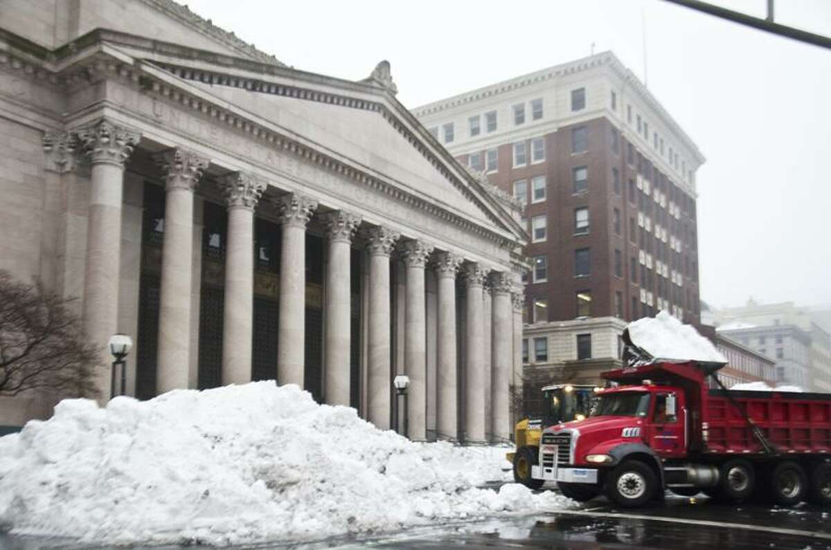 New Haven- A payloader dumps snow into a truck for removal on church Street across from the Gree. Melanie Stengel/Register