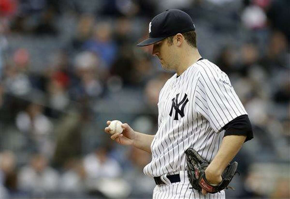 New York Yankees starting pitcher Phil Hughes looks at the ball before manager Joe Girardi removes him from the baseball game in the fourth inning against the Baltimore Orioles at Yankee Stadium in New York, Saturday, April 13, 2013. (AP Photo/Kathy Willens)