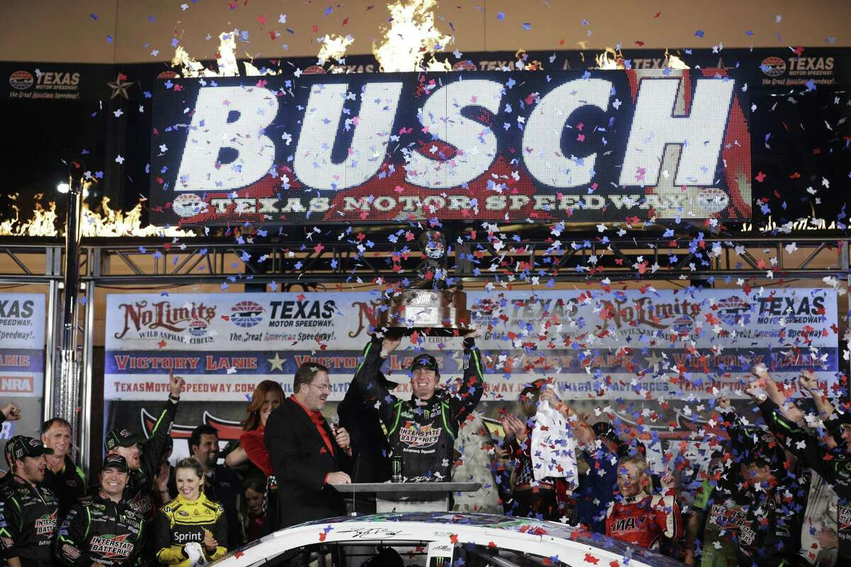 Sprint Cup Series's Kyle Busch (18) raises the trophy after winning the NASCAR Sprint Cup series NRA 500 auto race at Texas Motor Speedway Saturday, April 13, 2013, in Fort Worth, Texas. (AP Photo/Tony Gutierrez)