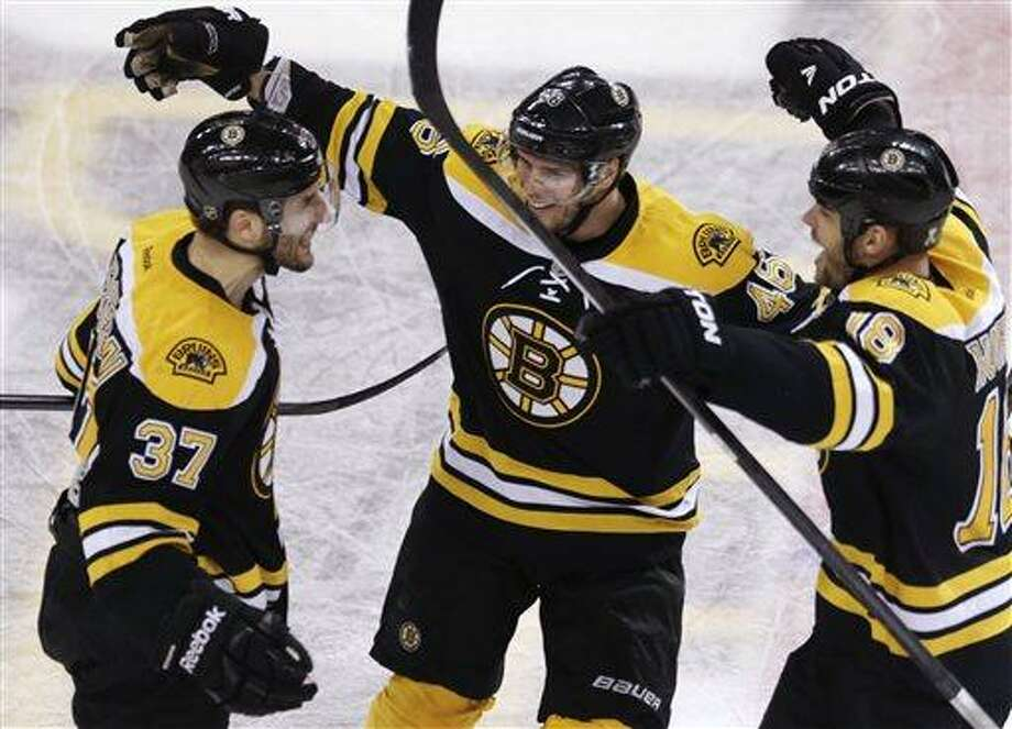 Boston Bruins center Patrice Bergeron, left, is congratulated by teammates David Krejci, center, and Nathan Horton, right, after his goal in the final minute of the third period, which tied the game 4-4 forcing overtime against the Toronto Maple Leafs, in Game 7 of their NHL hockey Stanley Cup playoff series in Boston, Monday, May 13, 2013. (AP Photo/Charles Krupa) Photo: AP / AP