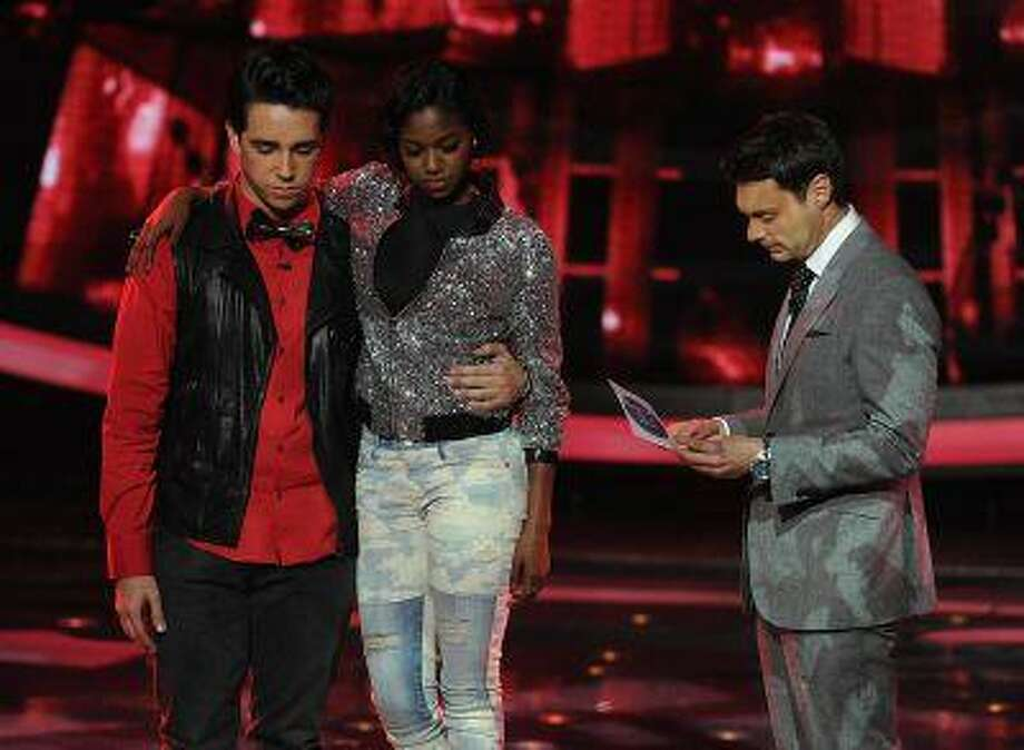 Ryan Seacrest announces that Lazaro Arbos, holding Amber Holcomb, is eliminated during 'American Idol' on Thursday, April 11, 2013. (Ray Mickshaw / FOX)