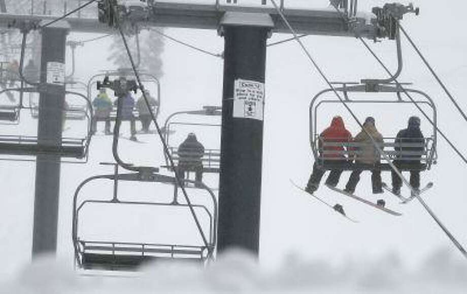 Skiers and snowboarders ride a lift in this 2010 file photo at Brighton Ski Resort in Big Cottonwood Canyon, Utah. Photo: ASSOCIATED PRESS / AP2010