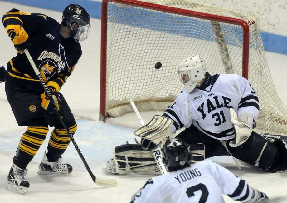 Quinnipiac at Yale, men's hockey, Ingalls Rink. Quinnipiac's first goal against Yale by Mike Dalhuisen (not pictured). QU's Jordan Samuels-Thomas left and Yale goalie Nick Maricic. Mara Lavitt/New Haven Register2/2/13