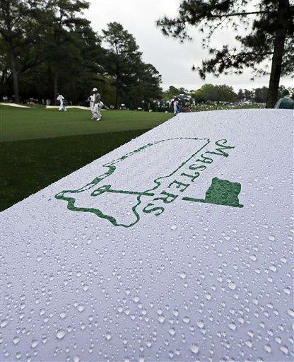 Golfers walk past an umbrella during a light rain storm during the second round of the Masters golf tournament Friday, April 12, 2013, in Augusta, Ga. (AP Photo/David J. Phillip)