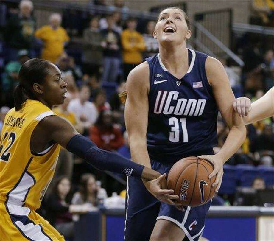 Connecticut's Stefanie Dolson (31) is fouled by Marquette's Sarina Simmons, left, during the first half of an NCAA college basketball game Saturday, Jan. 12, 2013, in Milwaukee. (AP Photo/Jeffrey Phelps) Photo: AP / FR59249 AP