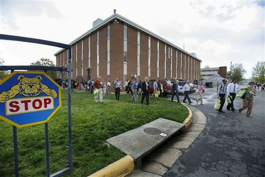 Students and faculty evacuate the North Carolina A&T State University campus at Drew Drive after a person reported seeing a man possibly with a rifle on the campus, Friday, April 12, 2013, in Greensboro, N.C. The university updated its website Friday morning to advise that students should stay inside and lock their doors and windows. (AP Photo/News & Record, Jerry Wolford) Photo: AP / News & Record
